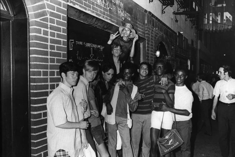 An unidentified group of young people celebrate outside the boarded-up Stonewall Inn (53 Christopher Street) after riots over the weekend of June 27, 1969. The bar and surrounding area were the site of a series of demonstrations and riots that led to the formation of the modern gay rights movement in the United States.